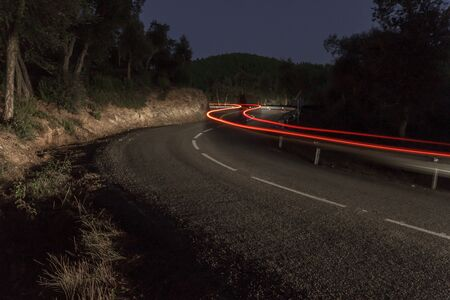 A car leaves a trail of light imprinted on a nightly image when passing through a curve of the road Zdjęcie Seryjne
