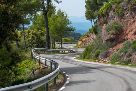 Picturesque, lonely  and zigzagging mountain road, surrounded by trees and nature