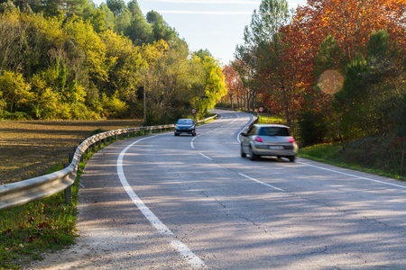 (Porqueres, Catalonia - November 14, 2015) -  Cars circulating along  a picturesque and lonely road, surrounded by trees and nature Publikacyjne