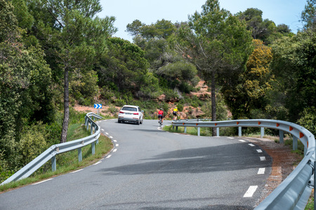 (Mura, Catalonia - May 25, 2018) - A vehicle overtakes two cyclists in a curve, on a very narrow and winding rural road