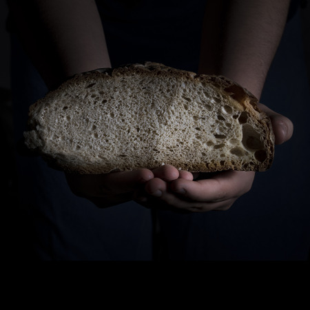 Hands sharing a sliced loaf of bread photo