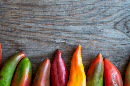 kilos: Peppers on Wooden Background with Copy Space