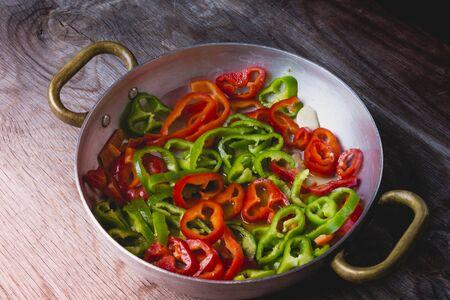 Peperoni verdi e rossi che friggono in una padella
