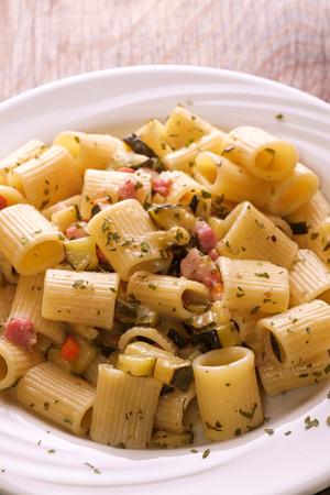 Rigatoni pasta with bacon and zucchini