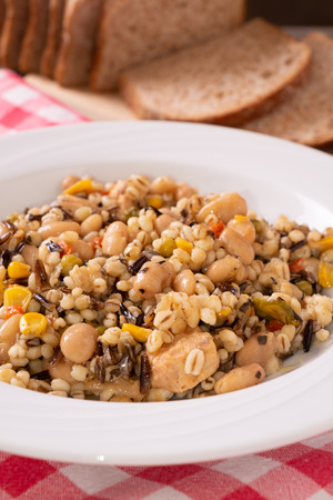 Spelled, chickpea, tuna and corn salad arranged on rustic table with bread