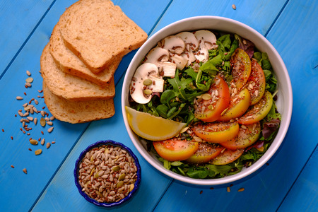 Top view of a bowl of mixed salad with tomatoes, mushrooms, lettuce and seeds with bread on a wooden table Banco de Imagens