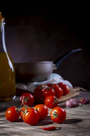 Cherry tomatoes on old wooden table with garlic, hot pepper and oil Stock Photo