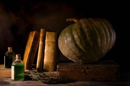 A witch's desk with magic potions, pumpkin and old books Stock Photo