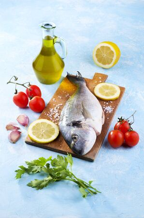Freshly caught and cleaned sea bream ready to be cooked together with tomatoes, garlic, oil and parsley
