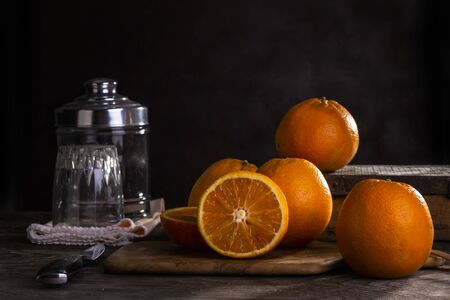 Oranges on wooden table with a dark background