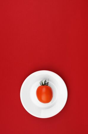 Cherry tomato on white plate placed on a red background