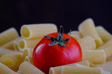 Tomato laid on Italian rigatoni pasta with dark background Stock Photo