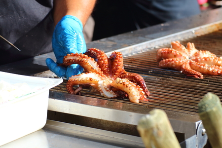 Cook cleans and prepares an octopus for cooking on the grill 版權商用圖片