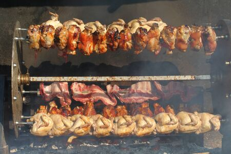 Village festival with electric rotisserie full of pork and chicken.