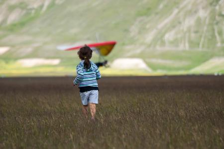 descriptive colours: child running towards a hang glider