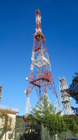 low angle view of two telecommunications towers against the sky Фото со стока