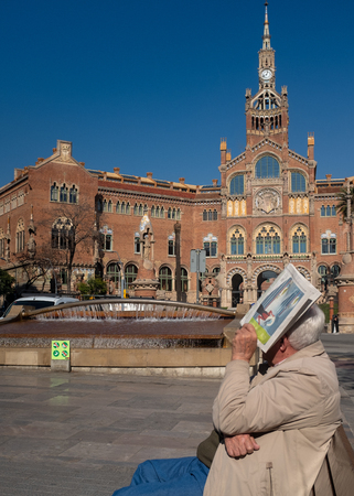 An elderly man is sitting on a bench and covers his face with a newspaper, he seems to look towards the main facade of the Hospital of the Holy Cross and St. Paul, Barcelona, Spain Editorial