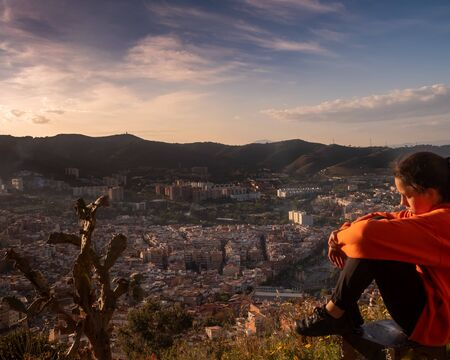 Sad girl sitting on the hill, embracing her knees and looking away at sunset, sadly depressed teen spending time alone, thoughtful young girl feeling lonely or frustrated thinking about problems. Stockfoto - 132049441