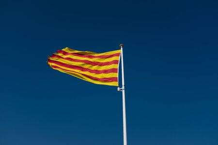 Low angle view at Catalonian flag with torn edges waving over clear sky.