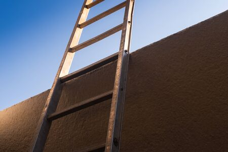 Low angle view of metal ladder leaning against concrete wall, the background is a clear sky. Conceptual themes of overcoming obstacles, challenges and new opportunities. 스톡 콘텐츠