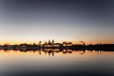 A deliberately overexposed panoramic photography of Mantova (Mantua, Italy). Cityscape at sunset reflected in water surface of Inferior Lake, the least deep of the three artificial lakes created to defend the city, a very important work of hydraulic engineering made more than 800 years ago. Imagens