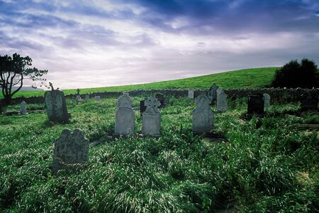 Ancient desolated cemetery located a short distance from the Atlantic coast in Ireland. Gravestones from different historical periods, lush grass, dark and overcast sky.