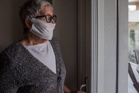 Side view of an old lady standing next to the window of her house. Contagion control measures urge the elderly population to stay at home so as to avoid contact with other people. Stockfoto