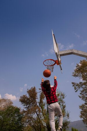 Rear view of a 8-9 years old boy, mid air, shooting jump shot on basketball court. The child has brown hair and is clothing a red sweatshirt. Positive emotion and energy. Vertical composition and copy space.