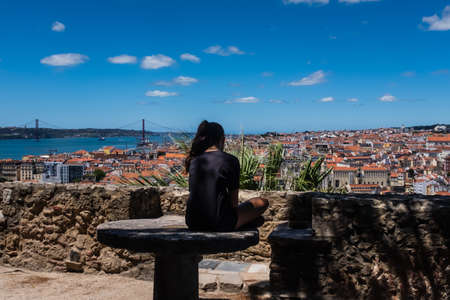 Lisbon, Portugal, girl sitting cross-legged on a stone table . Teenager spending her time alone, pensive young girl feeling lonely.