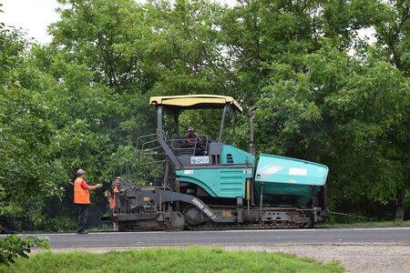 paver: A green paver working on road repairs