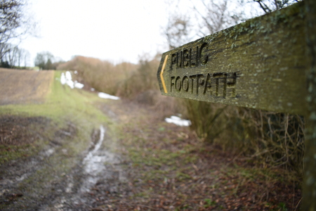 Wooden public footpath sign taken with a shallow depth of field, pointing towards a muddy path with the last signs of snow nestled against a hedgerow on a cold winter morning.