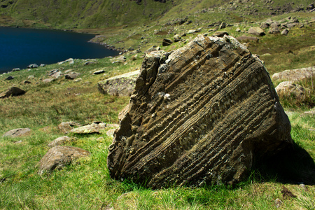 Layering within a lump of sedimentary rock resting on a hillside above a reservoir in the Lake District, UK.