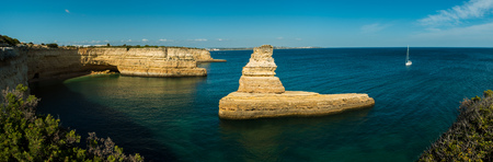 Panorama of the Yellow Submarine Rock on the Algarve Coast of Portugal, in the bay of Praia da Morena, with a sailing boat heading towards it under a clear blue sky. Stock Photo