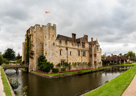 HEVER CASTLE, ENGLAND, UK – SEPTEMBER 08 2018: View of Hever Castle and its moat on a cloudy day, with a flag flying at full mast.