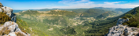 Panorama of the Duilhac-sous-Peyrepertuse commune in the Aude department in southern France, showing the valley beneath Peyrepertuse castle, through the village of Duilhac and across to Cucugnan. Stock Photo