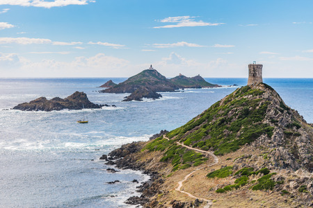 View of Pointe de la Parata on the west coast of Corsica. A ruined Genoese tower sits on top of the rocky promontory overlooking the archipelago of the Sanguinaires and a sailing boat on a sunny day.