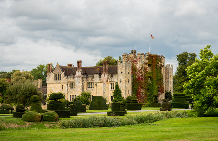 HEVER CASTLE, ENGLAND, UK – SEPTEMBER 08 2018: View of Hever Castle and its topiary garden on a cloudy day, with a flag flying at full mast. Hever Castle was the childhood home of Anne Boleyn. 報道画像