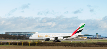 GATWICK AIRPORT, ENGLAND, UK – DECEMBER 09 2018: An Emirates Airline A380 Airbus taxis after landing at London Gatwick Airport, with the air traffic control tower in the background. Copy space. 報道画像