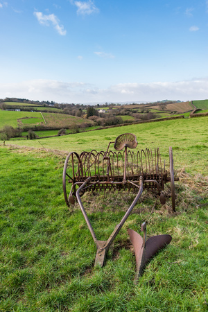 Old rusty horse drawn hay rake in a grass field with Devonshire countryside and hills in the background under a blue and cloudy sky on a bright day, with plenty of copy space included. Portrait orientation. Banco de Imagens