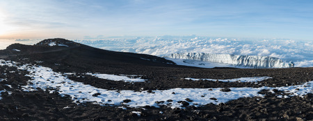 Panoramic view of a glacier sitting above the clouds at the summit of Mount Kilimanjaro taken at sunrise, with unidentifiable people climbing the path on the left towards Uhuru peak at the volcano top