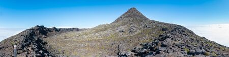 Large panoramic view of the pit crater rim and the pinnacle of the stratovolcano Mt Pico on Pico Island of the Azores. At 2351m, the summit is the highest point of Portugal. Blue sky above the clouds. Stock Photo