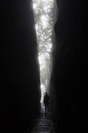 Silhouette d'une grande femme méconnaissable alors qu'elle regarde depuis une fente spectaculaire dans les rochers des montagnes de l'île de Madère. La lumière forme une forme de V avec un chemin qui la traverse. Banque d'images