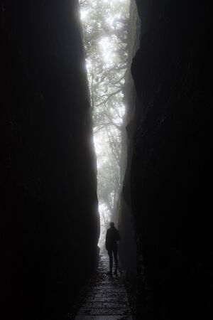 Silhouette of a tall unrecognizable woman as she looks out from a dramatic cleft in the rocks of the mountains of Madeira island. The light forms a V shape with a path passing through. Banque d'images
