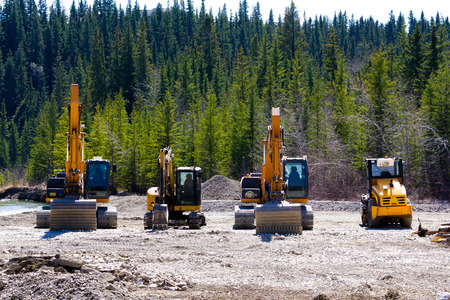 earth moving: Line up of earth moving machines during construction in the forest