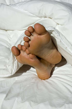 bare women: A couple of feet sticking out of a feather duvet