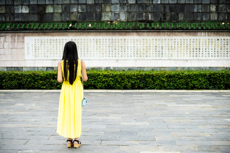 Lady in a yellow dress photographing a chinese temple
