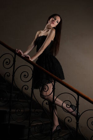 neo gothic: Black cocktail dress on the stairs