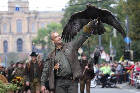 aguila real: Un hombre con un águila de oro de tomar parte en el desfile anual del traje tradicional en el primer fin de semana de la Oktoberfest en Munich, Baviera el 20 de Sept el año 2015