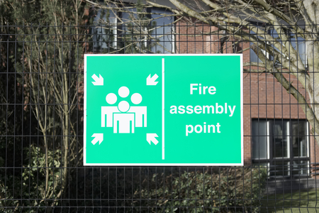 Fire assembly point sign at office factory workplace for security safety of workers people employees