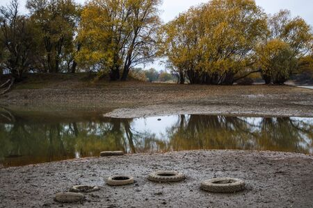 On the banks of the river are car tires. Environmental pollution. Cloudy autumn weather Фото со стока